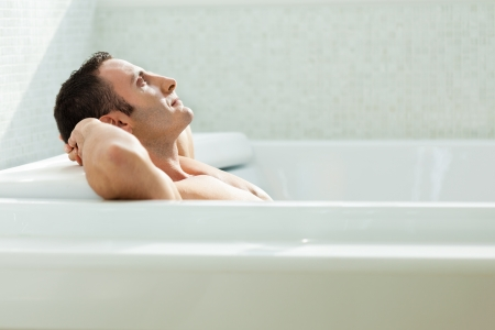 bathtub: a very muscular and fit man relaxing in a luxury bathtub