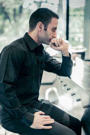 preoccupation: a sad, handsome man sitting at a bar with a pensive attitude