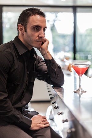 lonelyness: a sad, handsome man sitting at a bar with a pensive attitude
