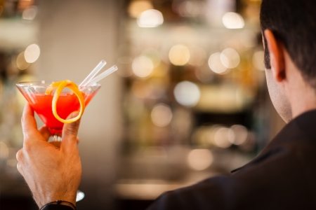 a distinguished young man holding a cocktail and celebrating Stock Photo