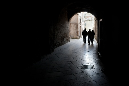 Three guys walking together in a little street in a village in Italy photo
