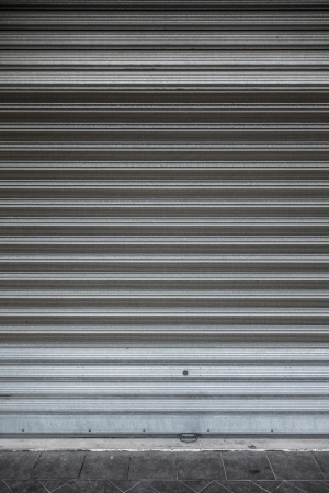 a shuttered roll up metal door with stains and scratches