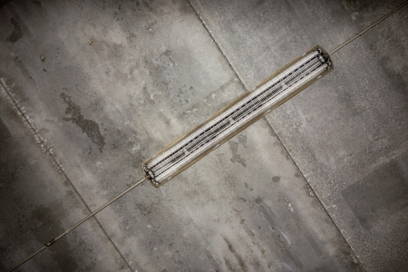 a fluorescent tube hanged on a concrete grungy ceiling photo