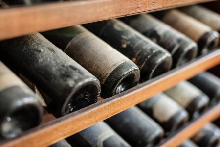 古代のワインのボトル、地下セラーの中に散布