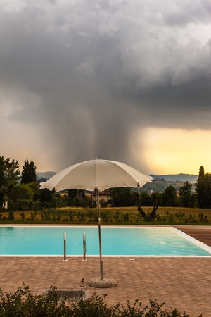 a parasol near the edge of a swimming pool and a storm in the background Stock Photo - 20427007