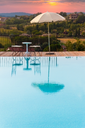 a beautiful and luxurious tuscany swimming pool with parasols and chairs photo