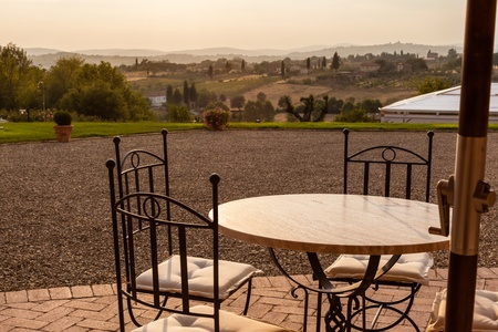 a luxurious resort in tuscany with tables, umbrellas and chairs photo
