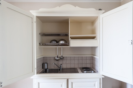 a small kitchen contained inside a wood cabinet photo