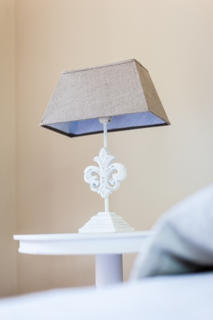 a bed side table with a classical style bed lamp on it photo