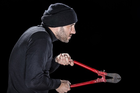 a burglar wearing black clothes holding huge wire cutters over black background Stock Photo - 20505837