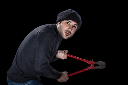 a burglar wearing black clothes holding huge wire cutters over black background Stock Photo - 20505737