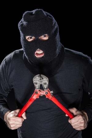 a burglar wearing a balaclava holding huge wire cutters over black background Stock Photo - 20505896
