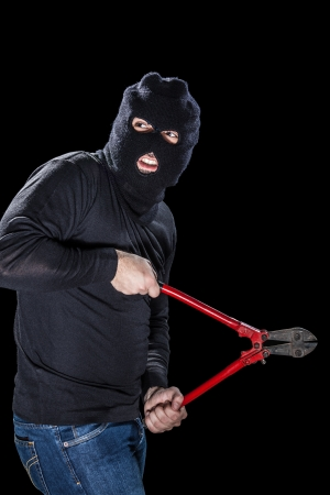 furtive: a burglar wearing a balaclava holding huge wire cutters over black background