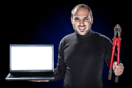breakin: a burglar or a cyber criminal holding a laptop with blank monitor and big red shears