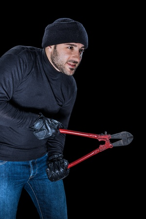 wire cutters: a burglar wearing black clothes holding huge wire cutters over black background