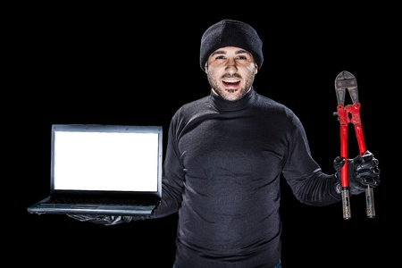 furtive: a burglar or a cyber criminal holding a laptop with blank monitor and big red shears