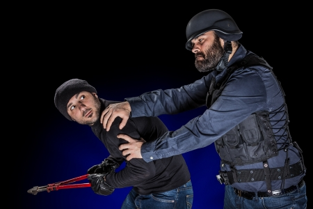 arresting: a cop wearing the SWAT tactical vest arresting a burglar Stock Photo