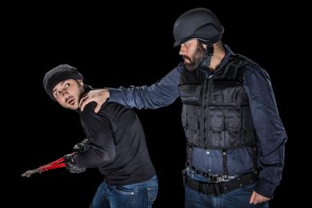 furtive: a cop wearing the SWAT tactical vest arresting a burglar Stock Photo