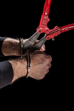 criminales que tratan de romper las esposas con un gran par de tijeras photo