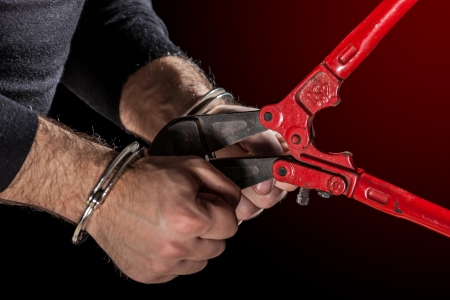 breakin: criminals that try to break handcuffs with a big pair of shears Stock Photo