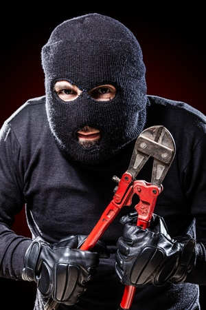 wire cutters: a burglar wearing a balaclava holding huge wire cutters over black background