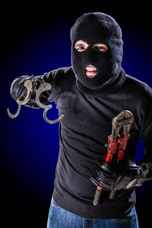 a burglar jailbreaking with a pair of opened handcuffs in his hand Stock Photo - 20505977