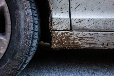 detail of a car wheel and some mud tainting the car