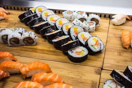 some maki sushi arranged in rows on wooden boards Stock Photo - 20563699