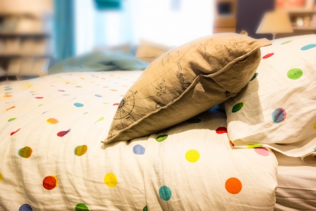 a comfortable bed with pillows and warm bedclothes