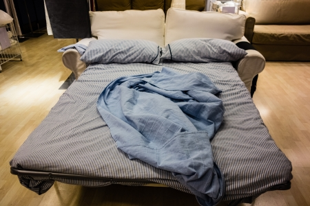 lying on bed: an opened sofa bed with bed clothes and pillows