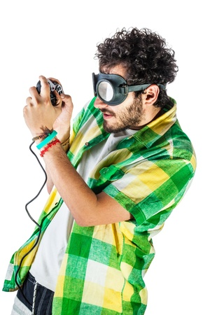 a guy wearing casual clothes and on old pair of goggles over a white bachground and using a gamepad controller