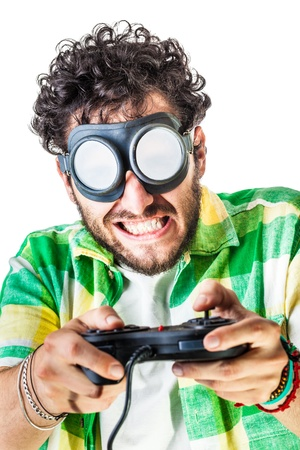 a guy wearing casual clothes and on old pair of goggles over a white bachground and using a gamepad controller photo
