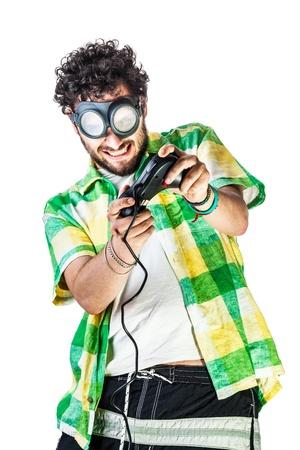 steampunk goggles: un hombre con ropa casual y el viejo par de gafas en un bachground blanco y usando un gamepad Foto de archivo