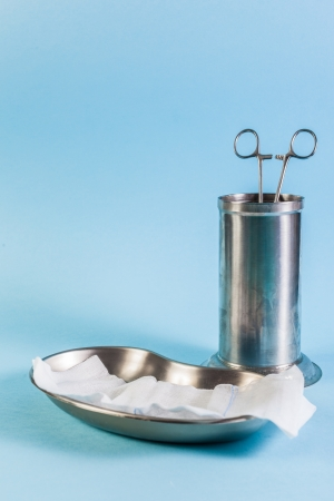 tiffany blue: a metallic surgical tray with gauze and a cylindric container with surgical forceps inside