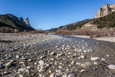 ramble: a nearly dried torrent bed with slopes in background Stock Photo