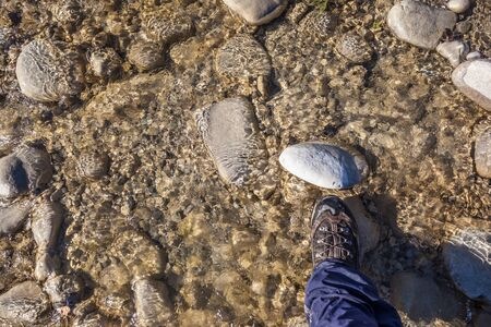 subjective: a hiking boot on a rock in the water stream of a small torrent