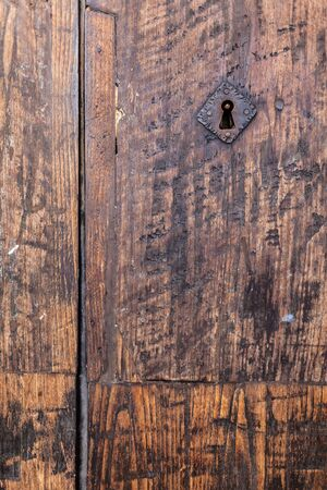 keylock: an old wooden and grungy locked door typical of the south of italy Stock Photo
