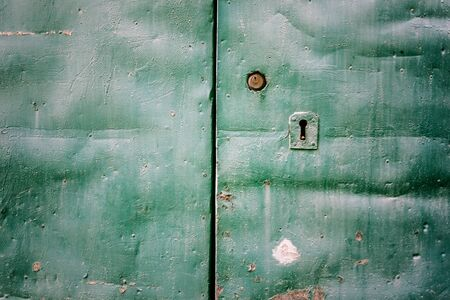 an old, rusty and grungy metal door with a keyhole photo