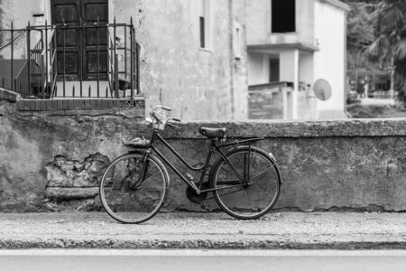an old bicycle parked in a dirty italian alley way Stock Photo - 20564273
