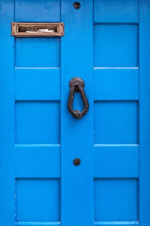 a blue wooden door with a door knocker and a full letter box photo