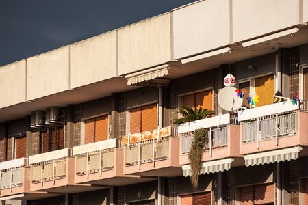 gentrification: the facade of an old and neglected building with balcony Stock Photo
