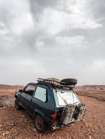 a dirty and small 4x4 car parked in the sahara desert with two fuel tank mounted on the back photo
