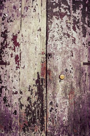 an old, rusty wooden door with lot of scratches and peeling paint photo