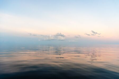 clouds making: a pastel coloured tropical dawn with some fluffy clouds making reflections in the calm waters