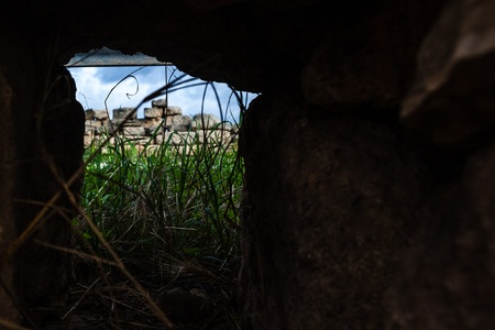 a grass field seen through a hole in a stone wall photo