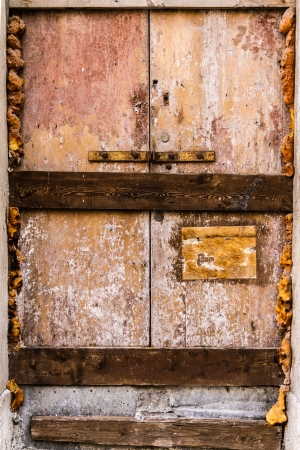 a rusty, abandoned and boarded up old door photo
