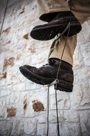 rope ladder: a old fashioned caver climbing up a rope ladder
