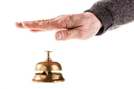 a mature old man ringing a hoted reception bell isolated over white photo