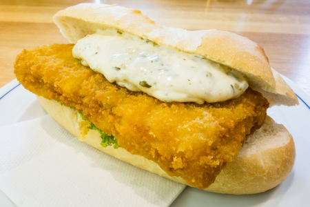 close up of a tasty fried fish cutlet sandwich with lettuce and tartar sauce Stockfoto
