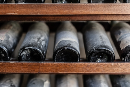 a row of ancient and tasteful dusty wine bottles in a cellar
